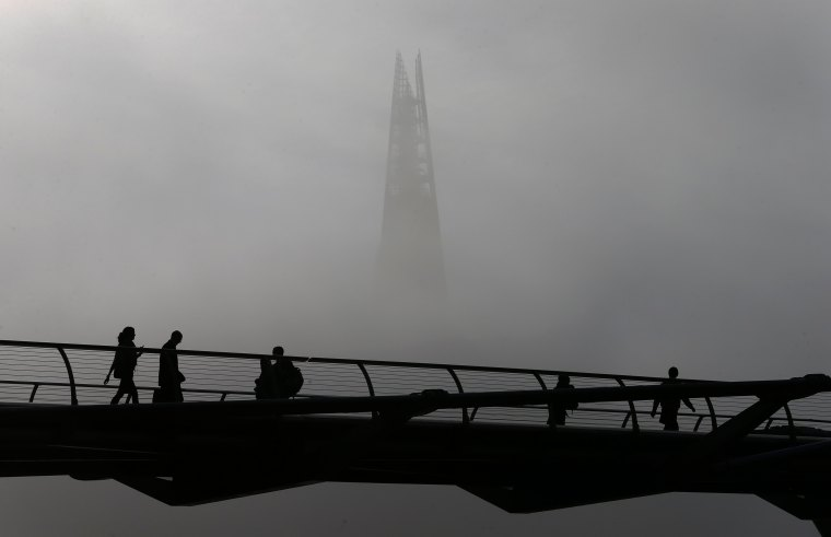 People walk cross the Millennium footbridge in front of the Shard on a foggy morning in London