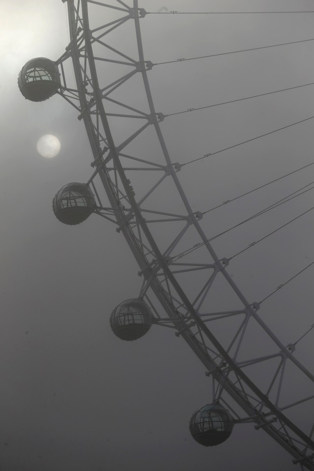 The sun emerges through the mist around the London Eye on a foggy morning in London