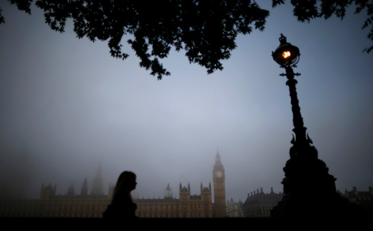 A woman walks along the south bank of the Thames opposite the Houses of Parliament on a foggy morning in London