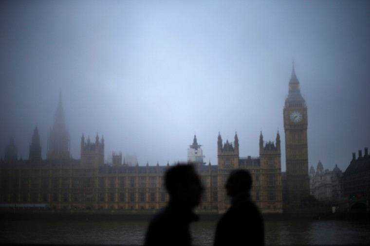 Commuters walk long the south bank of the Thames opposite the Houses of Parliament on a foggy morning in London