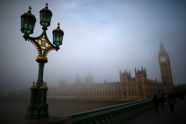 Commuters walk accross Westminster Bridge towards the Houses of Parliament on a foggy morning in London