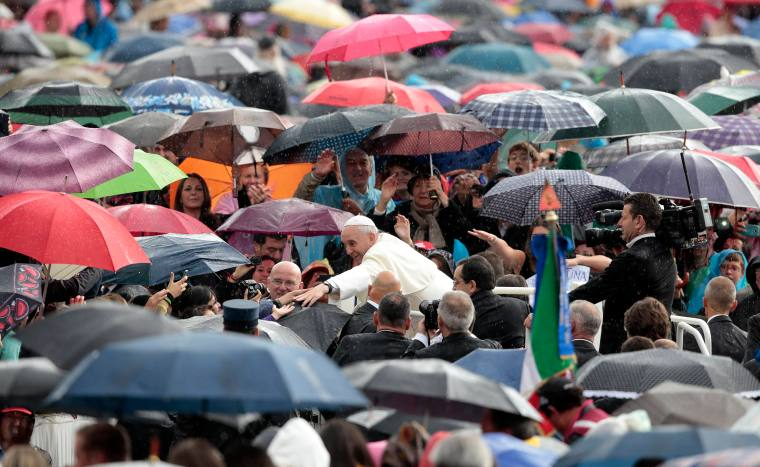 Pope Francis shake hands as he arrives to leads the weekly audience at Saint Peter's square in Vatican
